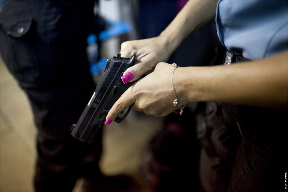 Элейн Соарес Консейо, офицер из Полиции проверяет свое оружие. Так она готовится выйти на патрулирование в Complexo do Caju, в новую «усмиренную» фавелу в северной зоне города.