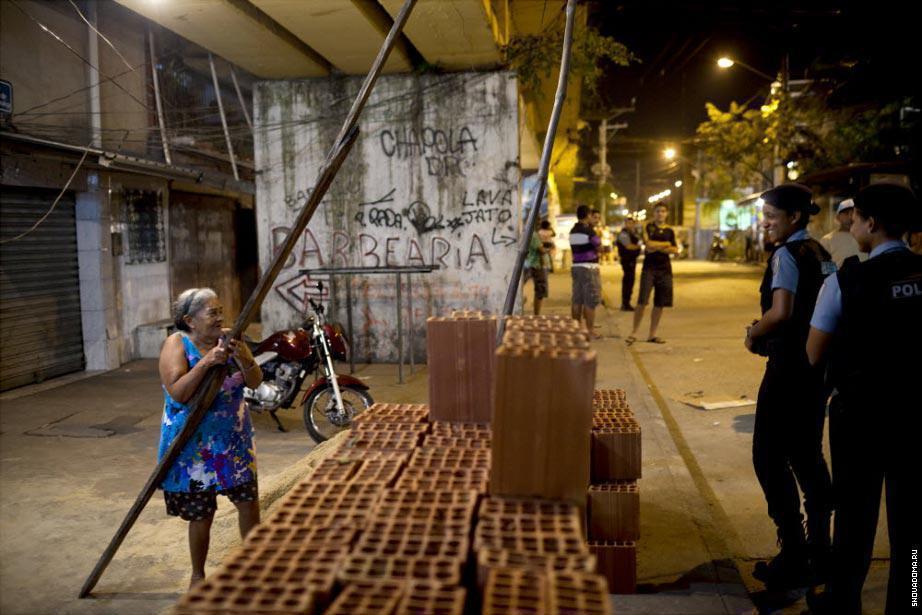 Офицеры из Полиции Тамара Фонтела, 26 лет (слева)и Алине Хервано, 28 лет (справа) разговаривают с пожилой женщиной во время патрулирования Complexo do Caju.