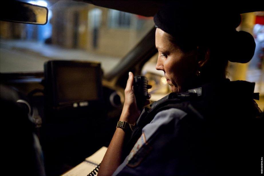 Карла Бонн, офицер из Полиции использует радиосвязь во время патрулирования в полицейской машине в районе Complexo do Caju.