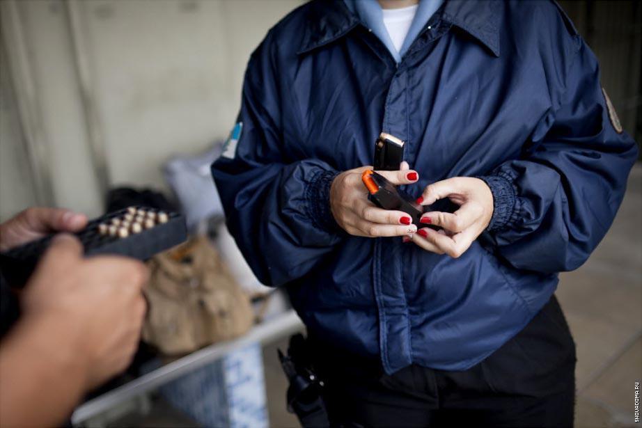 Офицеры из Полиции готовят свое оружие перед патрулированием.