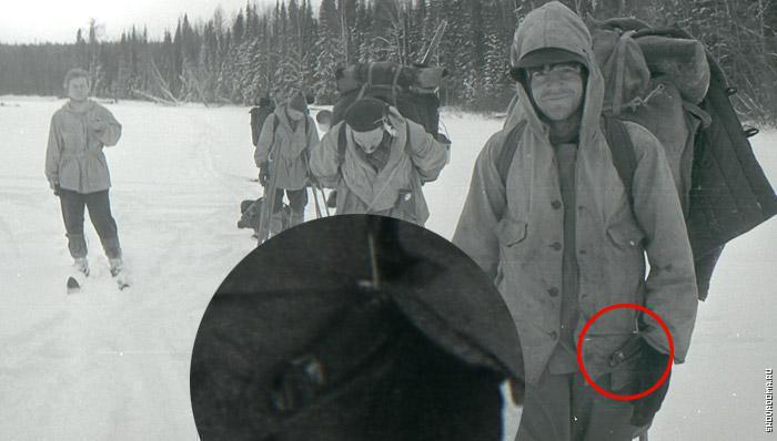 """Фрагмент снимка №9 из фотоплёнки №3. При внимательном рассмотрении можно видеть на левом боку Николая Тибо-Бриньоля самодельный нож """"финского"""" типа, подвешенный к карману самодельным приспособлением вроде крючка.  На рукоять ножа и крючок указывают стрелочки. Можно видеть даже часть гарды (упора, предотвращающего соскальзывание руки на лезвие). Нож подвешен """"под правую руку"""", что свидетельствует о том, что Тибо был правшой."""